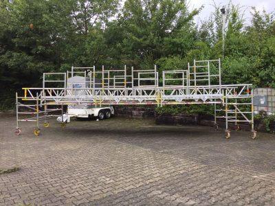10,30m langes Spezial-Rollgerüst. Dieses Gerüst wurde gebraucht, um über einer Rolltreppe zu arbeiten. Auf dem Bild ist unser Test-Aufbau zu sehen, um sicher zu stellen das die gewünschte Spezialkonstruktion auch funktionieren wird. Das Gerüst wurde anschließend von uns beim Kunden vor Ort aufgebaut.